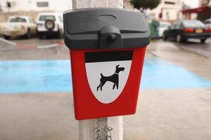 caixa vermelha com pacotes para cocô de cachorro ao ar livre foto