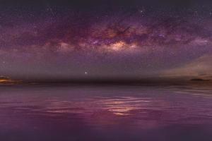 Cenário noturno com a Via Láctea colorida e amarela clara cheia de estrelas no céu no verão belo universo de fundo do espaço foto