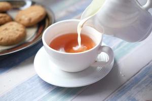 perto de derramar leite em uma xícara de chá foto