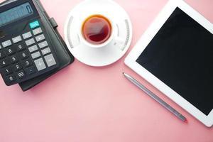 composição plana de tablet digital e escritório estacionário em fundo rosa foto