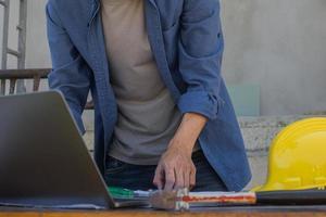 empregado trabalhador trabalhando por tecnologia de computador na construção do local foto
