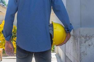 engenheiro segurando capacete na construção do local foto