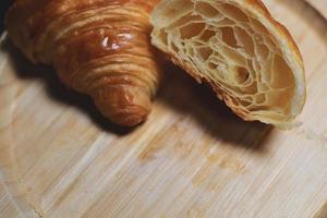os croissants são colocados sobre um fundo de madeira. produtos assados em fundo isolado foto