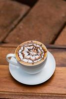 café quente latte art na mesa de madeira, hora de relaxar foto
