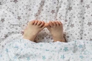close-up dos pés da menina na cama, debaixo do cobertor foto