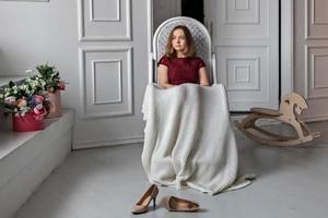 jovem adolescente sentada em seu quarto em uma cadeira de balanço, coberta com um cobertor foto