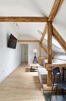 apartamento no sótão, sala de estar moderna, design interior do apartamento com vigas de madeira rústicas antigas, pisos e móveis. foto
