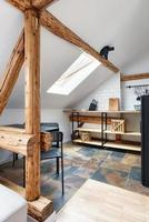 apartamento no sótão, cozinha moderna, design interior do apartamento com vigas e móveis antigos de madeira rústica, cerâmica de granito italiano elegante. foto