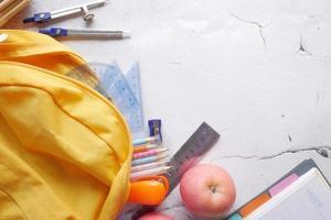 conceito de volta às aulas com mochila amarela e material escolar na mesa foto