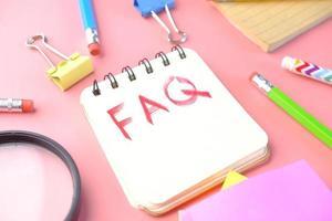 mão desenhando texto faq no bloco de notas em fundo rosa foto