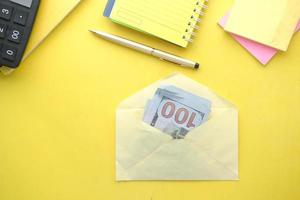 close-up de dinheiro em dólares americanos em um envelope sobre fundo amarelo foto