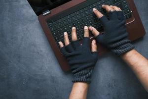 mão do hacker roubando dados do laptop, visualização de cima para baixo foto