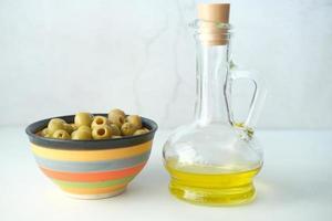 garrafa de azeite e azeitona fresca em um recipiente na mesa foto