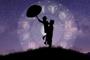 casal cantando e dançando sobre a roda do zodíaco e o fundo da Via Láctea foto