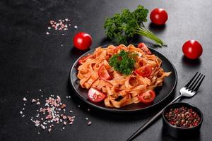 deliciosa pasta fresca com molho de tomate com especiarias e ervas em um fundo escuro foto