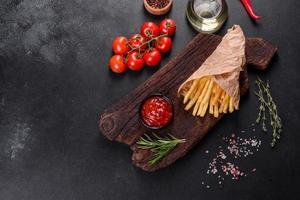 Batatas fritas saborosas frescas e molho vermelho em uma tábua de madeira foto