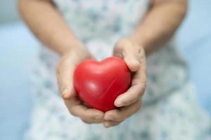 paciente asiático sênior ou idosa senhora segurando um coração vermelho na mão na cama na enfermaria do hospital de enfermagem, conceito médico forte e saudável foto