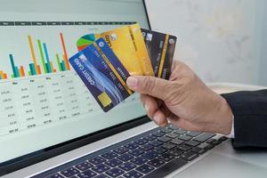 contador asiático trabalhando, calculando e analisando a contabilidade do projeto de relatório com notebook e cartão de crédito no conceito moderno de escritório, finanças e negócios. foto