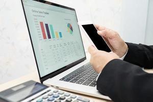 contador asiático trabalhando e analisando contabilidade de projeto de relatórios financeiros com gráfico gráfico, telefone celular e calculadora no conceito moderno de escritório, finanças e negócios. foto