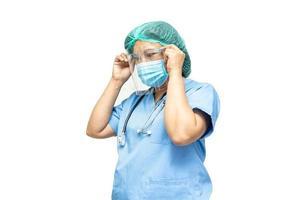 médico asiático usando máscara, protetor facial e terno novo normal isolado no fundo branco com traçado de recorte para proteger o coronavírus covid-19 da infecção de segurança. foto