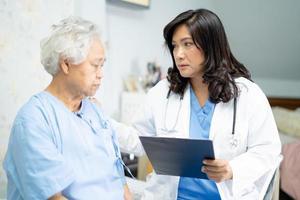 médico falando sobre diagnóstico e nota na área de transferência com mulher idosa asiática sênior ou idosa enquanto estava deitado na cama na enfermaria do hospital de enfermagem, conceito médico forte e saudável. foto