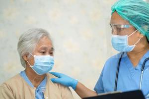 médico asiático usando protetor facial e terno novo normal para verificar o paciente protege o surto de coronavírus covid-19 de infecção de segurança na enfermaria de quarentena do hospital. cobiçado, positivo, paciente, enfermeira, corona, novo normal, doença, ppe, foto