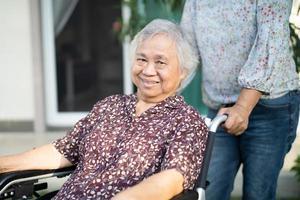 ajuda e cuidados paciente idoso asiático ou idoso senhora sentada na cadeira de rodas em casa, conceito médico forte saudável. foto