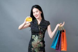 Mulher asiática usa vestido tradicional chinês com sacola de compras e cartão de crédito foto