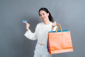 linda mulher asiática com sacolas de compras e apresentando cartão de crédito foto