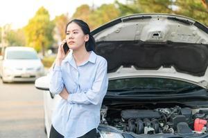 jovem em pé perto de um carro quebrado com capô aberto, tendo problemas com o veículo foto