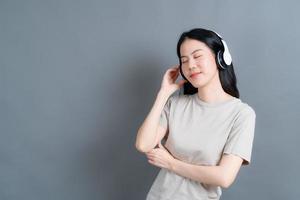 jovem asiática ouvindo música com fones de ouvido foto