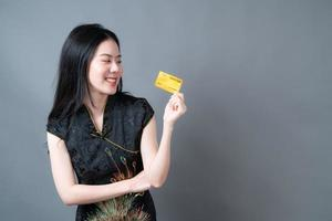 Mulher asiática usando vestido tradicional chinês com a mão segurando um cartão de crédito foto