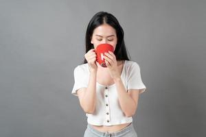 jovem mulher asiática com um rosto feliz e uma mão segurando uma xícara de café foto
