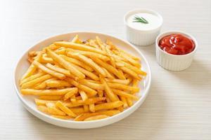 batatas fritas com creme de leite e ketchup foto