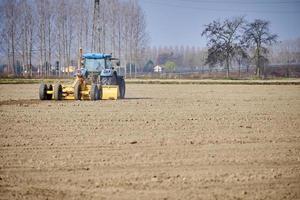 um trator agrícola trabalha em um campo recém-arado foto