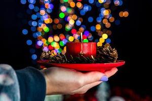 segurando vela decorada de natal foto