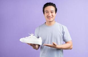homem asiático segurando tênis no fundo roxo foto