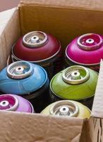caixa cheia de latas de spray coloridas foto