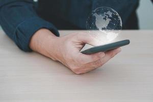mão segurando o telefone móvel com conexão de rede global, mão homem com terra virtual no fundo desfocado. foto