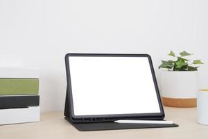 tablet de tela em branco com lápis digital em cima da mesa. foto