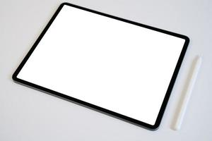 maquete de tablet e lápis digital com tela em branco na mesa branca. foto