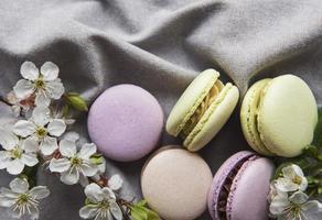 variedade colorida de macaroons doce francês em um fundo cinza têxtil foto