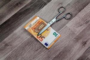 corte notas de 50 euros com uma tesoura foto