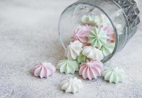 pequenos merengues brancos, rosa e verdes no copo foto