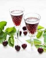 licor de cereja no copo e frutas frescas foto