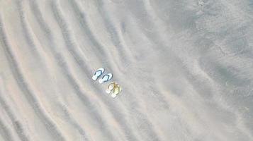 chinelos na praia de areia, plano de fundo das férias de verão, vista aérea de cima foto