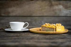 xícara de café com sobremesa em uma mesa de madeira foto