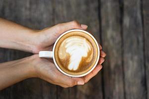 mãos femininas segurando uma xícara de café no fundo da mesa de madeira foto