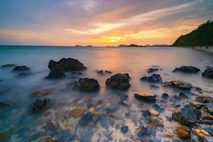 foto de longa exposição de rochas no mar ao pôr do sol