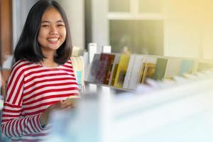 menina asiática em pé e sorrindo lendo um livro em livrarias foto